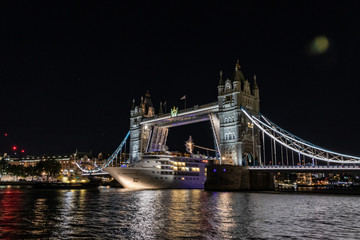 beautiful picture of the Tower Bridge in London at night with open gates for a big cruise ship, London, UK.