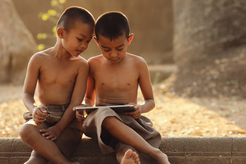 Two Asian boys are interested in learning different things on their tablets. The concept of distance education via the internet.