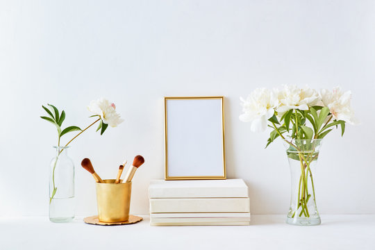 Home interior with decor elements. Gold frame, white peonies in a vase, cosmetic set