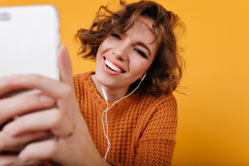 Close-up portrait of pleased white woman with casual makeup taking picture with her phone. Smiling magnificent girl using smartphone for selfie on orange background.
