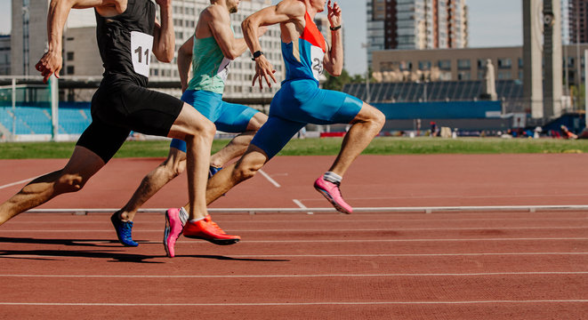 men sprinters run on track stadium in athletics competition