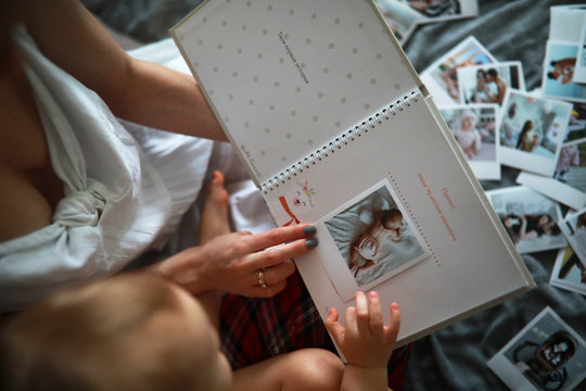 Mother sits and looks photo album with her baby.