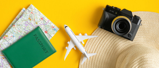 Travel accessories on yellow background. Flat lay vintage camera, beach hat, map, passport, airplane. Top view with copy space. Summer holiday travel planning concept