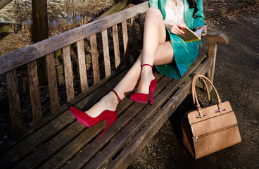 Wall Mural - Woman reading a book with red shoes sitting on the bench. Leather hand bag on the floor.