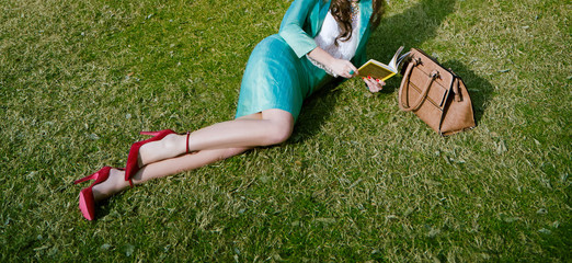Wall Mural - Beautiful legs woman wearing red shoes heels and handbag. Reading book on the grass