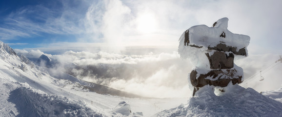 Fototapeta Whistler, British Columbia, Canada. Beautiful Panoramic View of Statue on top of Blackcomb Mountain with the Canadian Snow Covered Landscape in background during a cloudy and vibrant winter sunset. obraz