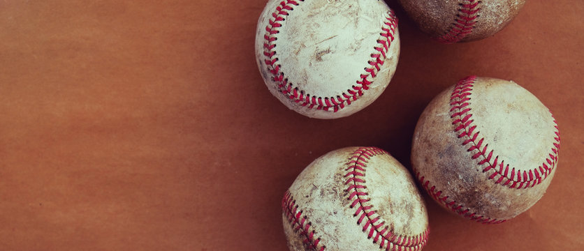 Retro sports banner shows group of old used baseballs with copy space by balls.  Vintage baseball concept.