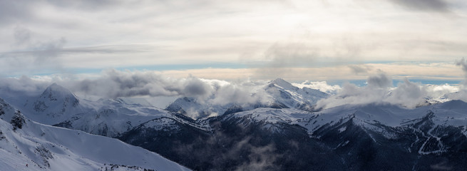 Wall Mural - Whistler, British Columbia, Canada. Beautiful Panoramic View of the Canadian Snow Covered Mountain Landscape during a cloudy and vibrant winter day.