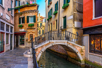 Wall Murals Gondolas Narrow canal with boat and bridge in Venice, Italy. Architecture and landmark of Venice. Cozy cityscape of Venice.
