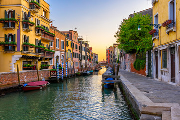 Wall Mural - Narrow canal with gondola and bridge in Venice, Italy. Architecture and landmark of Venice. Cozy cityscape of Venice.