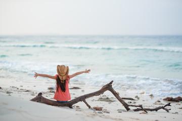 ビーチで流木に座る女の子