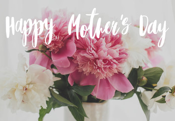 Happy Mother's day text handwritten on lovely peony bouquet in sunny light on rustic window sill. Stylish pink and white peonies in vase. Happy Mothers day greeting card Fotomurales