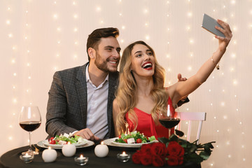 Romantic couple using smartphone, to take salfie on date at restaurant