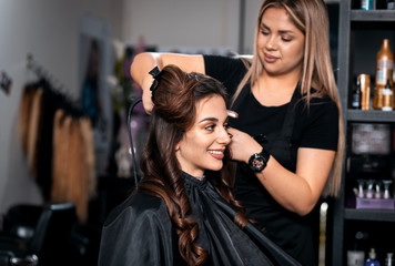 Female hairdresser makes hairstyle on young woman with brunette hair in salon.