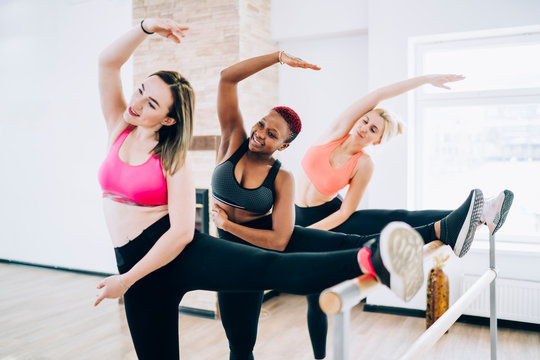 Diverse women stretching muscles on ballet barre