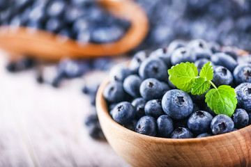 Blueberries in wooden bowl with mint leaf on top. Blueberry forest fruit close up or detail on white board. Fotomurales