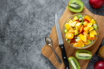 Top view of healthy fruits salad - mango, citrus, kiwi fruit, plum and persimmon. clean eating. Copy space.