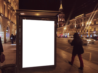 billboard in a bus stop. Glowing box with an advertising poster standing in the city at night. With people walking and riding cars