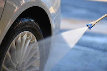 Car wheel washing. Cars cleaning with water jet. Rim wash close up.