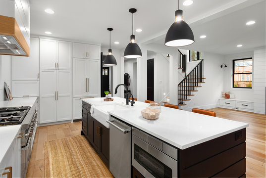 Beautiful white kitchen with dark accents in new modern farmhouse style luxury home. Features large island with farmhouse sink, dishwasher, microwave and view of living room and stairs.