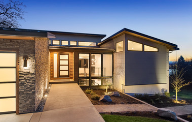 Beautiful modern style luxury home exterior at sunset with glowing interior lights.