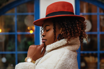 Outdoor close up portrait of young elegant African American woman wearing stylish wrist watch, orange hat,white winter faux fur coat, posing in street, near blue window. Copy, empty space for text Wall mural