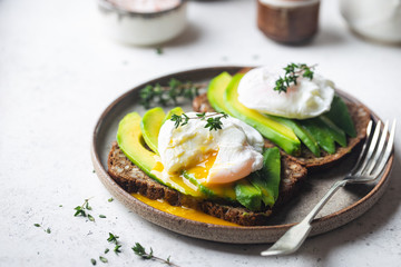 Healthy breakfast whole wheat toasted bread with avocado and poached egg over white background Fototapete
