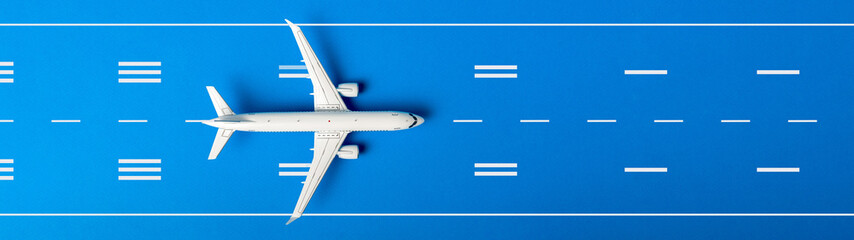 White plane, airplane on blue color runway background. Top view, flat lay. Summer travel, vacation concept. Banner