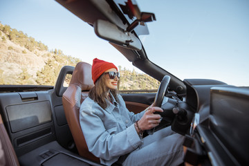 Happy woman dressed casually in jacket and red hat driving convertible car on the beautiful mountain road