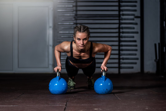 Young strong fit sweaty muscular girl with big muscles doing push ups on two big old heavy kettlebells with her hands for hard core cross workout training on the gym floor real people