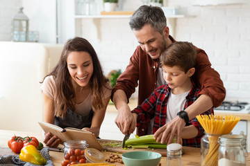 Mother, father, son chopping vegetables on kitchen