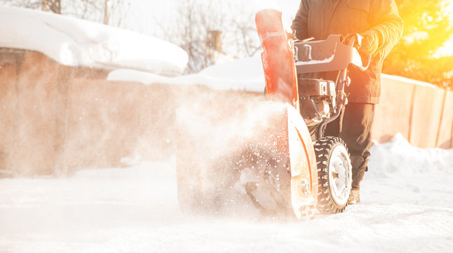 Man cleaning snow from sidewalks with snowblower machine winter
