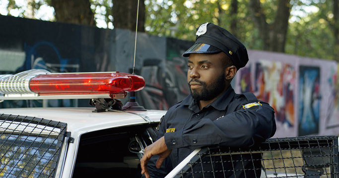 Portrait of handsome African American young policeman in uniform and cap. Front view of police officer smiling at camera outdoors. Cop on the background with police car and old lane.