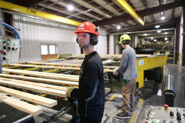 Workers inspect lumber at West Fraser Pacific Inland Resources sawmill in Smithers