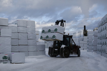 A worker uses a fork-lift to move pallets of finished lumber at West Fraser Pacific Inland Resources sawmill in Smithers