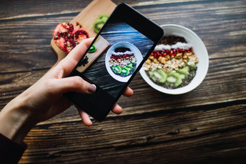 Woman holding a smartphone and taking a picture of a healthy smoothie bowl.
