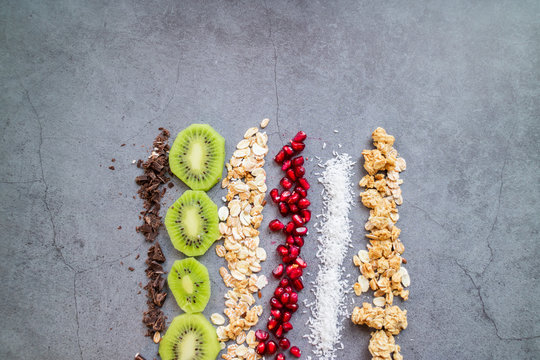 Chocolate, kiwi, oats, pomegranate, coconut and grains  isolated on concrete background. Top view.