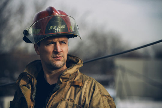 Male firerfighter with red helmet outside