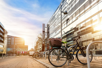 Bike parked near modern apartment residential buiding or college campus at downtown of european city street. Eco-friendly transport and healthy active lifestyle concept. Sustainable work commute