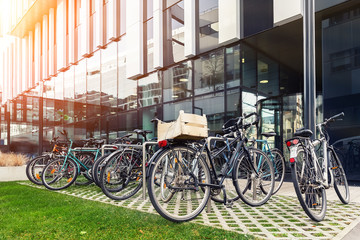 Foto op Plexiglas Fiets Many bike parked near modern apartment residential buiding or college campus at downtown of european city street. Eco-friendly transport and healthy active lifestyle concept. Sustainable work commute