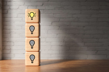 cubes with lightbulb symbols in front of a brick wall