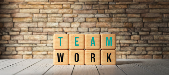 cubes with the word TEAMWORK in front of a brick wall