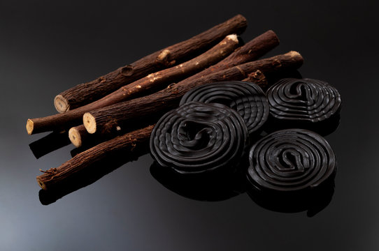 Chewy candy and delicious dessert concept with black licorice wheels or spirals flavoured with the extract of the root of the Glycyrrhiza Glabra plant roots sticks on shiny dark background