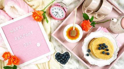 Pancake breakfast tray in bed with syrup and blueberries fruit creative layout flat lay top view, with letter felt board Happy Pancake Day message.