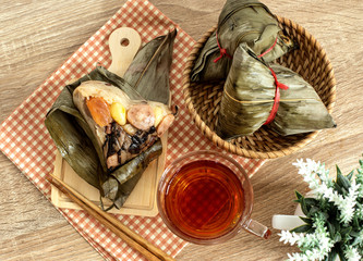 Close up Zongzi or rice dumpling on the wooden table with Chinese tea in Dragon Boat Festival, Asian traditional food