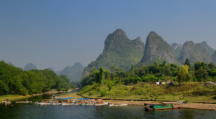 Tuinposter Guilin Tour boat rafts on the shore of the Li river Guangxi China with karst mountain peaks