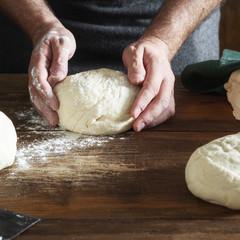 Fototapete - Man preparing dough for bread in bakery close up