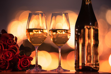 Wall Mural - two glasses of wine and bottle of wine on wooden table with roses