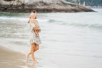 BEAUTIFUL Woman mother and baby daughter are walking along the seashore. Fashion and family style for a beach holiday.