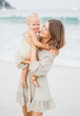 Close-up portrait of a woman and her child walking along the beach in summer. Family vacation and trendy style.